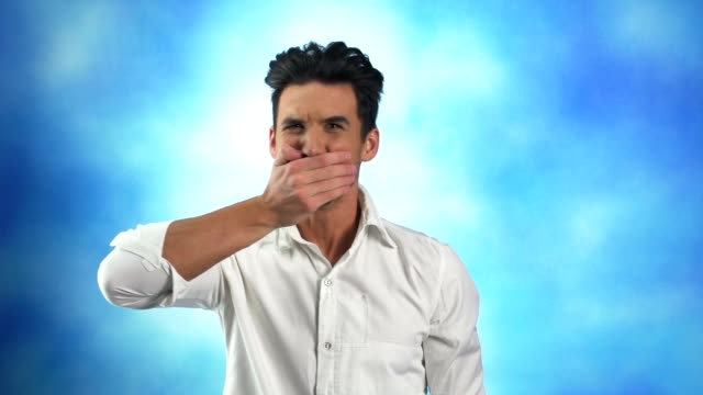 Young man covering mouth with hand, shaking head