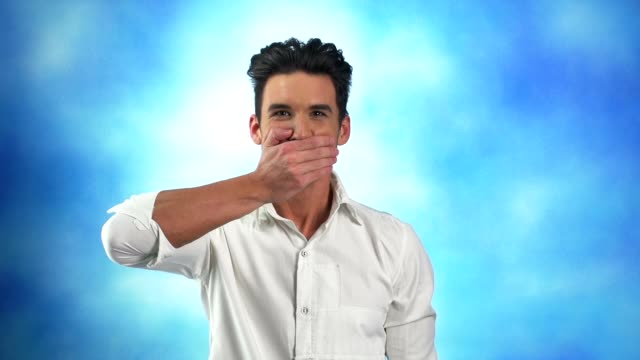 young man covers his mouth with a hand - hands covering mouth stock videos and b-roll footage