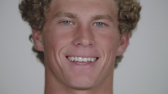 vídeos de stock e filmes b-roll de cu slo mo. young man cracks a smile for camera in white studio. - só um rapaz