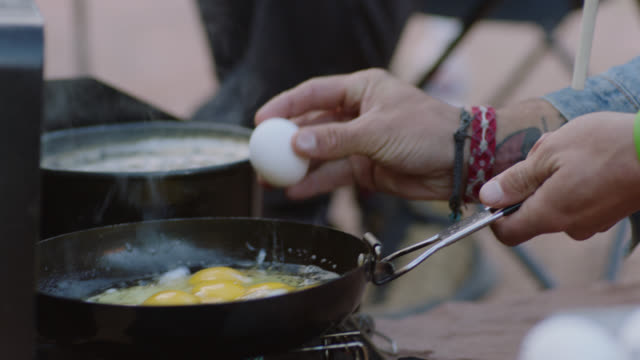 CU. Young man cracks egg over sizzling skillet on portable grill at camp site.