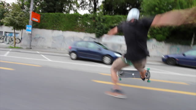 vídeos de stock e filmes b-roll de a young man crashes while longboard skateboarding downhill in a city. - impacto