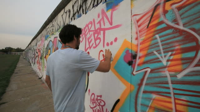 Young man creating Graffiti on Berlin wall