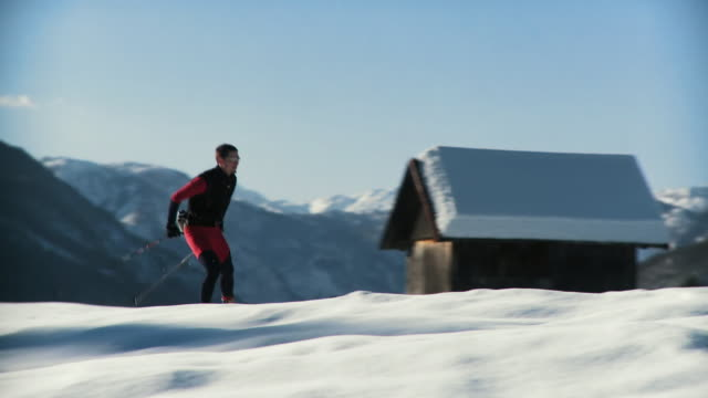 ws pan young man cross-country skiing, mountains covered with snow in the background / pokljuka, triglav national park, slovenia - triglav national park stock videos and b-roll footage