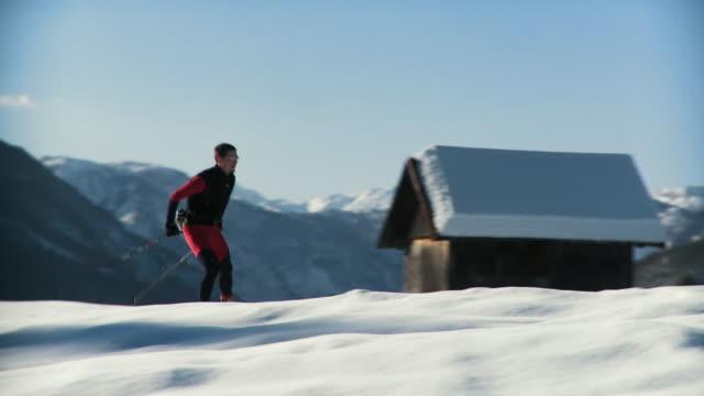 ws pan young man cross-country skiing, mountains covered with snow in the background / pokljuka, triglav national park, slovenia - längd bildbanksvideor och videomaterial från bakom kulisserna