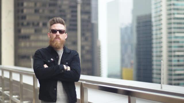 young man crosses arms and stares at camera on windy chicago high rise balcony. - endast en man i 30 årsåldern bildbanksvideor och videomaterial från bakom kulisserna