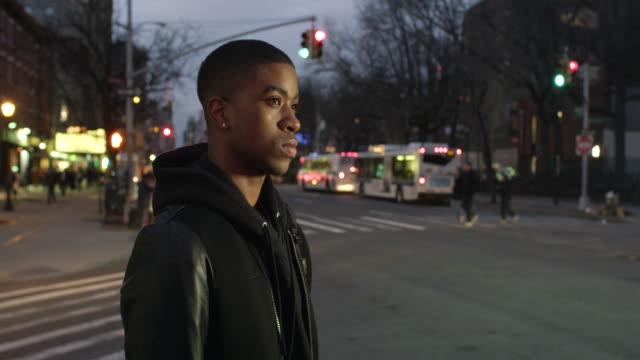 vídeos de stock e filmes b-roll de young man crosses new york street at night - cara para baixo