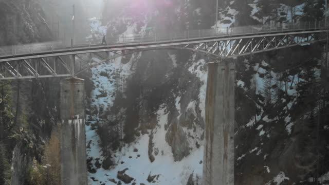 vidéos et rushes de jeune homme traversant le pont dans les alpes suisses - images de drone - traverser