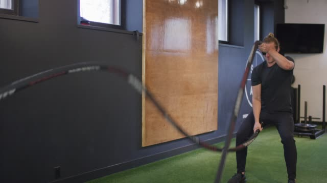 Young man cross-training with ropes