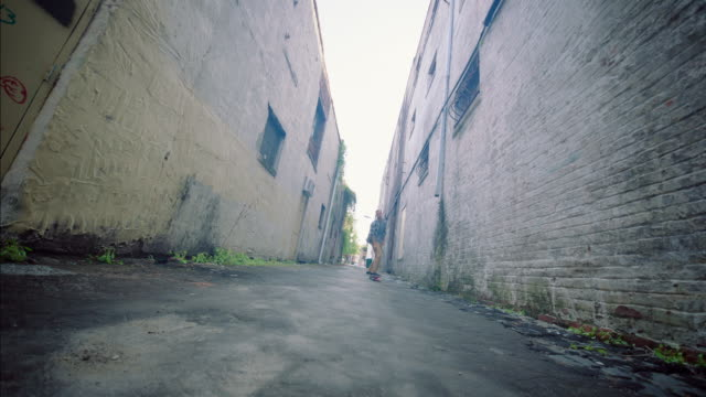 young man cruises up downtown alley on longboard - kryssa bildbanksvideor och videomaterial från bakom kulisserna