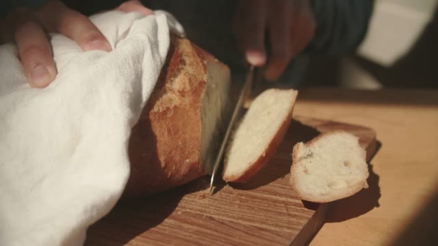 cu young man cutting a freshly made bread - bread stock videos & royalty-free footage