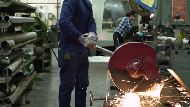 stockvideo's en b-roll-footage met young man cutting a pipe in a factory - metaalindustrie