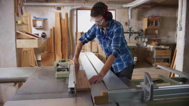 ds young man cutting a wooden plank on the table saw - one mid adult man only stock videos & royalty-free footage