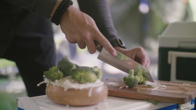 stockvideo's en b-roll-footage met jonge mens die broccoli op een snijraad voor ontbijt op kampeerreis snijdt. - sperzieboon