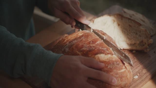 cu young man cutting fresh bread with a knife - brot backen stock-videos und b-roll-filmmaterial