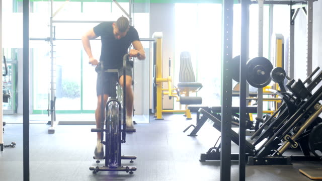 Young Man Cycling Fast on Fitness Bycicle