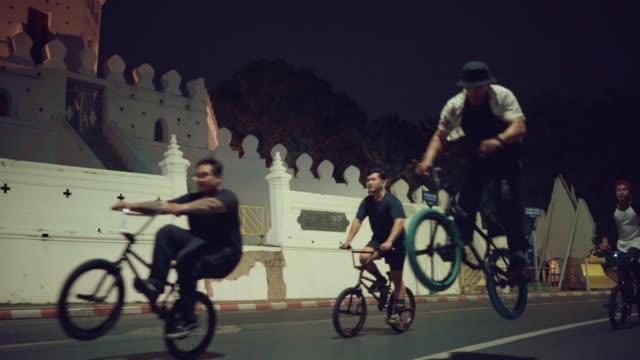 ung man cyklist gruppmöte på natten - sydostasien bildbanksvideor och videomaterial från bakom kulisserna