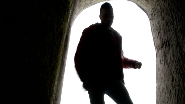 young man dancing in the cave doorway - doorway stock videos and b-roll footage