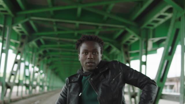 Junger Mann tanzen unter Brücke