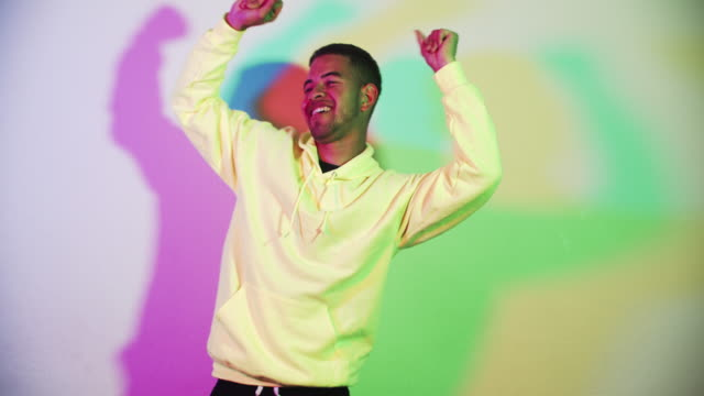 young man dancing with colorful background - short hair stock videos & royalty-free footage