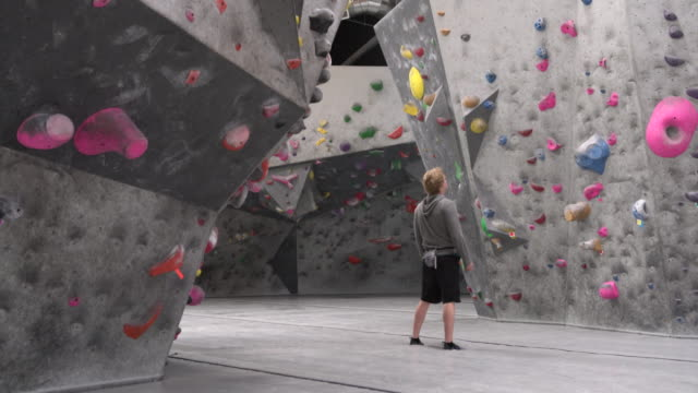 WS Young man deciding where to climb in front of a climbing wall