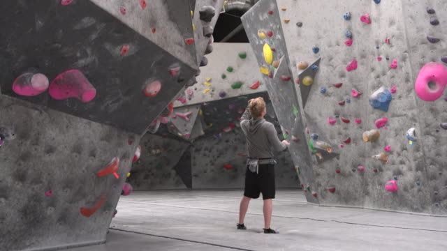 WS Young man deciding which path to take up a climbing wall