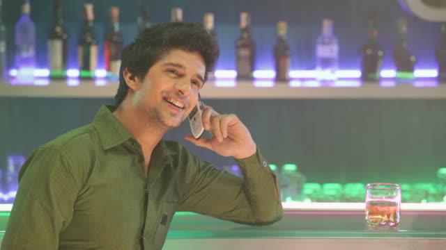 Young man dialing a mobile phone at bar counter