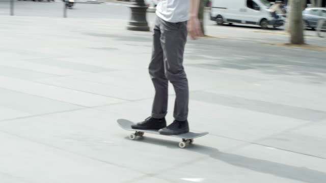 a young man does a skateboarding trick while riding his skateboard in a town square. - stunt stock videos & royalty-free footage