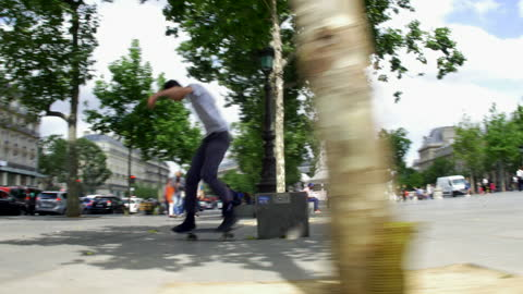vidéos et rushes de a young man does a skateboarding trick while riding his skateboard in a town square. - risque