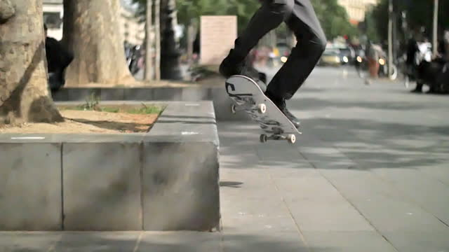 a young man does a skateboarding trick while riding his skateboard in a town square. - slow motion - stunt stock videos & royalty-free footage