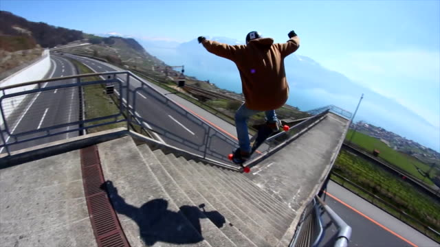 a young man does a trick on a skateboard down stairs. - extreme sports stock videos & royalty-free footage