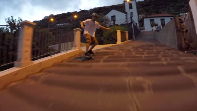 a young man does a trick on a skateboard down stairs. - hinunter bewegen stock-videos und b-roll-filmmaterial