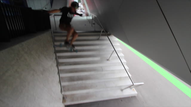 A young man does a trick on a skateboard down stairs.