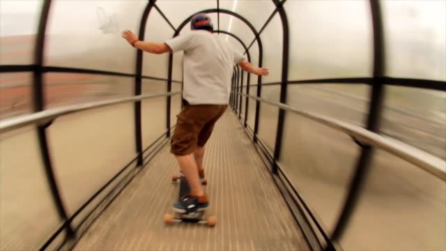 vídeos y material grabado en eventos de stock de a young man does a trick on a skateboard through a tunnel. - forbidden