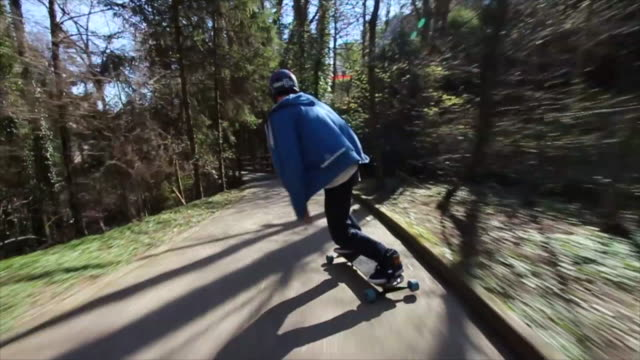a young man does some tricks on a skateboard while riding down a hill. - time-lapse - extremsport stock-videos und b-roll-filmmaterial