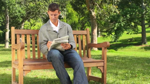 vídeos y material grabado en eventos de stock de young man doing a crossword on a bench / cape town, western cape, south africa - crucigrama