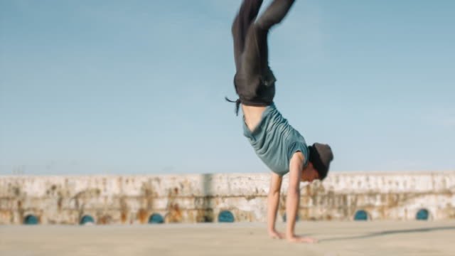Young man doing a handstand acrobat movement outdoors