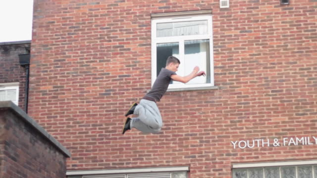 vidéos et rushes de a young man doing a parkour freerunning jumping and flipping stunt. - slow motion - model released - 1920x1080 - hd - mur brique