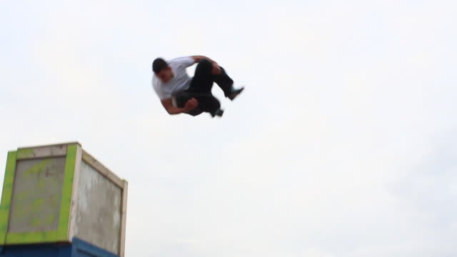 A young man doing a parkour freerunning jumping and flipping stunt. - Slow Motion - Model Released - HD