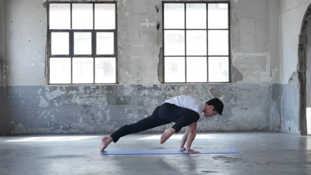 a young man doing basic yoga pose indoors - kopf nach hinten stock-videos und b-roll-filmmaterial