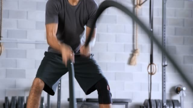 young man doing battle rope exercise in the gym - rope stock videos & royalty-free footage