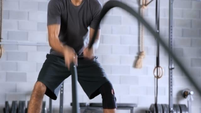 vídeos de stock, filmes e b-roll de jovem fazendo exercício de corda batalha no ginásio - cordão