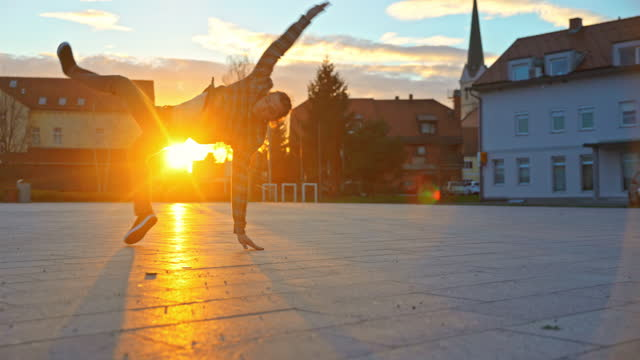 young man doing breakdance moves on street - stilig man bildbanksvideor och videomaterial från bakom kulisserna