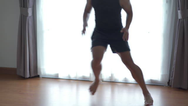 young man doing cardio exercise at home - bedroom stock videos & royalty-free footage