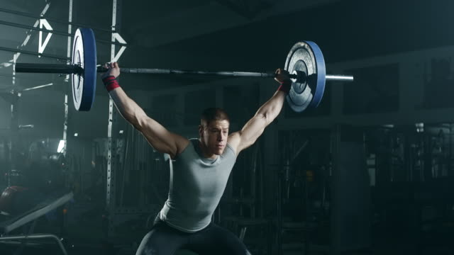 young man doing exercise with weights in gym - weight training stock videos & royalty-free footage