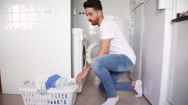vídeos de stock, filmes e b-roll de young man doing laundry in a gender equality domestic life situation - vestuário