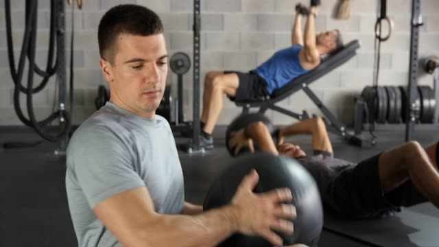 Young man doing medicine ball exercises in the gym
