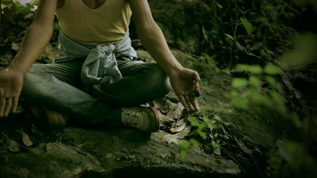 若い男性の瞑想ヨガを与えます。 - 胡坐点の映像素材/bロール