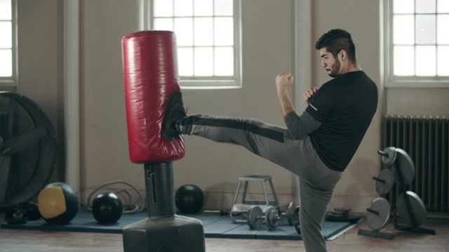 stockvideo's en b-roll-footage met young man doing mixed martial arts in a gym - oefenen