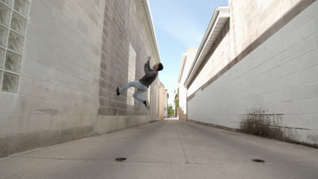 sm young man doing parkour in an alley way - sweatshirt stock videos & royalty-free footage