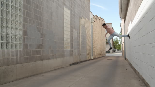 young man doing parkour in an alley way - nur junge männer stock-videos und b-roll-filmmaterial